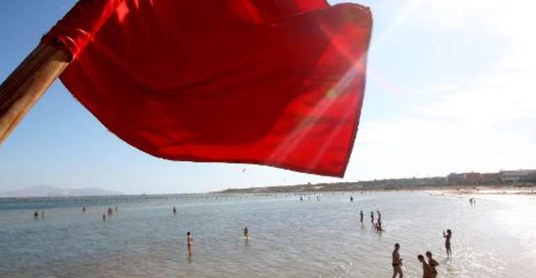 A red flag serving as a warning of shark sightings flutters over tourists on the beach in the Red Sea resort of Sharm el-Sheikh on December 8, 2010.  By  (AFP/File)
