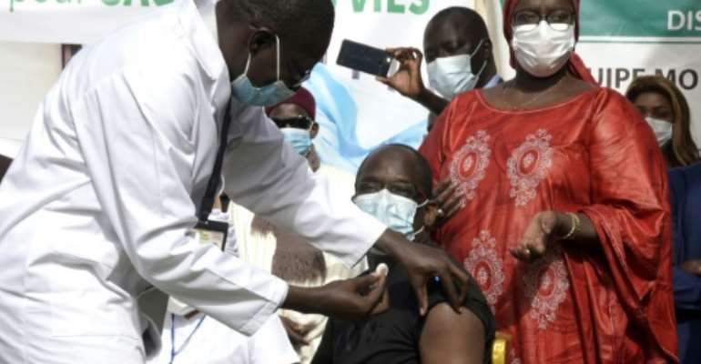 Getting the jab: Health Minister Abdoulaye Diouf Sarr becomes the first person in Senegal to be immunised against coronavirus. The banner reads 'Get vaccinated - protect yourself to save lives'.  By Seyllou (AFP)