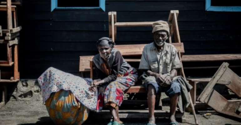 Going back: Two elderly people who fled Goma wait with their possessions for the ride home.  By GUERCHOM NDEBO (AFP)