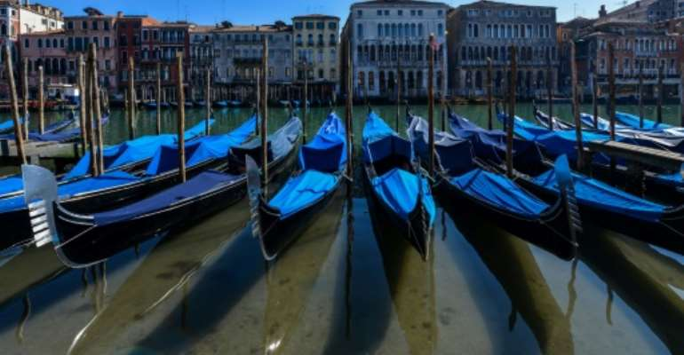 Gondolas sit empty in Venice's Grand Canal with Italy in lockdown to confront the dire impact of new coronavirus which, in one day, killed 475 more people in the country.  By ANDREA PATTARO (AFP)