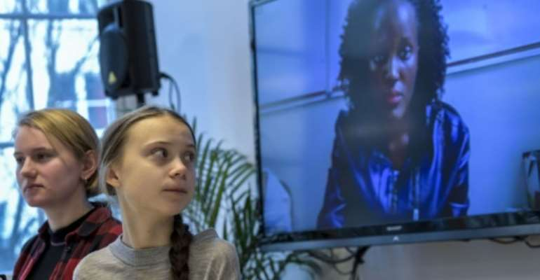 Greta Thunburg watches fellow eco warrior Vanessa Nakate, speaking from Kampala, after she was cropped out of a photo of young activists.  By Pontus LUNDAHL (TT News Agency/AFP)