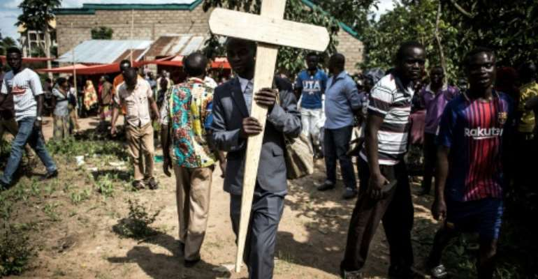 Grief: A relative of a woman killed in a suspected ADF attack in Beni carries a cross to her grave.  By John WESSELS (AFP)