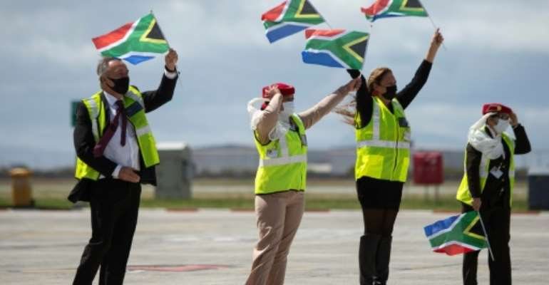 Ground crew wave flags as an Emirates airliner lands in Cape Town from Dubai, marking the end of South Africa's long ban on international flights.  By RODGER BOSCH (AFP)