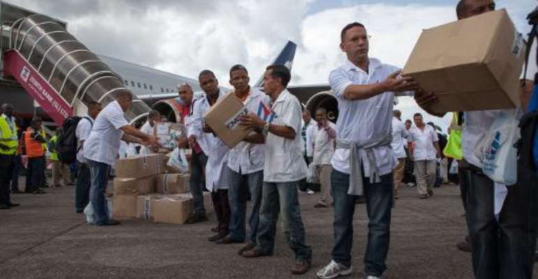 Members of a team of 165 Cuban doctors and health workers unload boxes of medical material upon their arrival in Sierra Leone to help fight Ebola on October 2, 2014.  By Florian Plaucheur (AFP/File)