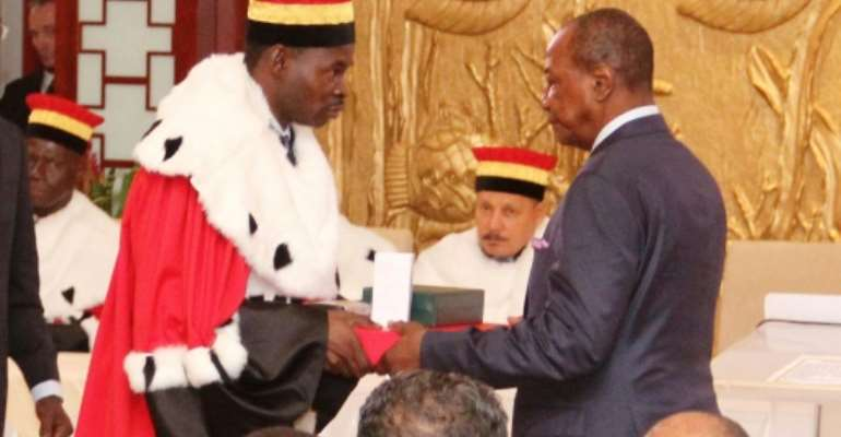 Alpha Conde (R) takes the oath of office for his second five-year term as president of Guinea at the Sekoutoureya royal palace in Conakry on December 21, 2015.  By Cellous Binani (AFP/File)
