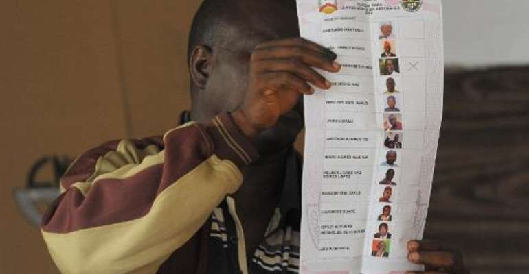 An election official shows a ballot at a polling station in Bissau, Guinea-Bissau, on April 13, 2014.  By Seyllou (AFP/File)