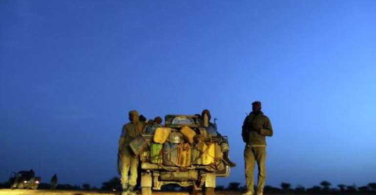 Malian soldiers patrol on a road between Kidal and Gao on July 29, 2013 in northern Mali.  By Kenzo Tribouillard (AFP/File)