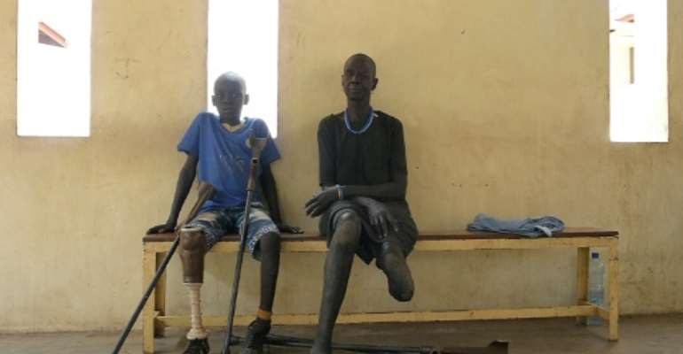 Gunshot wound survivors Jal Keat, 12, left, and Nyagn Thyuong, wait at the Red Cross rehabilitation centre in Juba.  By SIMON MAINA (AFP)