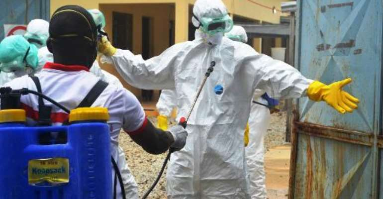 Guinea's Red Cross health workers prepare to carry the body of an Ebola victim at the Medecin sans frontieres treatement centre in Conakry on September 14, 2014.  By Cellou Binani (AFP/File)