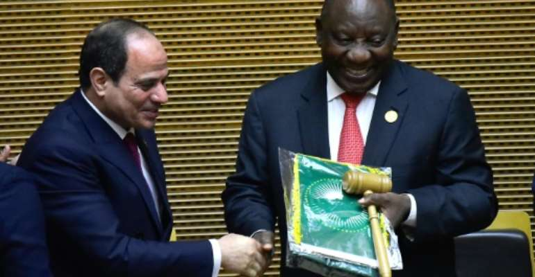 Handover: Outgoing AU chair Egyptian President Abdel Fattah al-Sisi, left, passes the baton to South African President Cyril Ramaphosa. Ramaphosa says settling the conflicts in Libya and South Sudan will be a priority of his tenure.  By MICHAEL TEWELDE (AFP)
