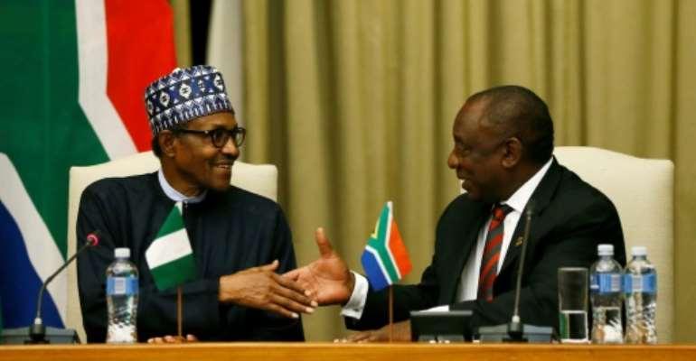 Handshake: Buhari, left, and Ramaphosa.  By Phill Magakoe (AFP)