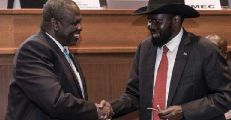 Handshake: South Sudan's president, Salva Kiir, right, and his former deputy turned rebel leader, Riek Machar, seal the peace deal in Addis Ababa last September.  By YONAS TADESSE (AFP)