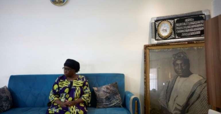 Hatouma Keita, Modibo Keita's daughter, poses next to a portrait of her father in Bamako.  By MICHELE CATTANI (AFP)