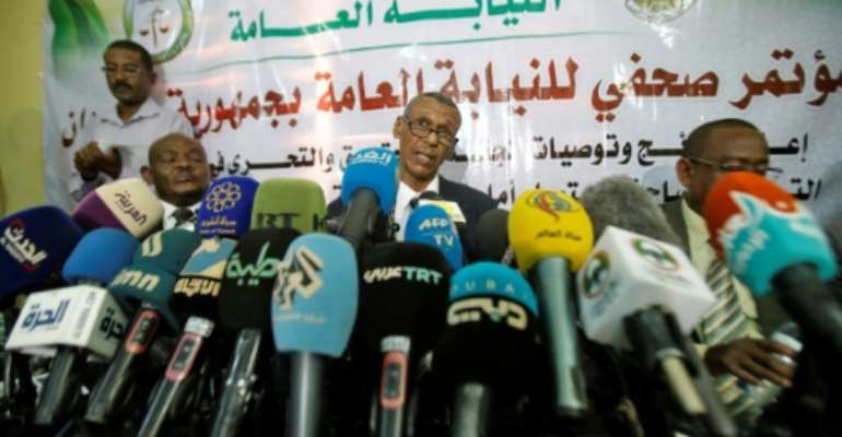 Head of a Sudanese investigative committee Fatah al-Rahman Saeed (C) reveals findings of a probe into the deadly raid on a Khartoum protest camp.  By ASHRAF SHAZLY (AFP)