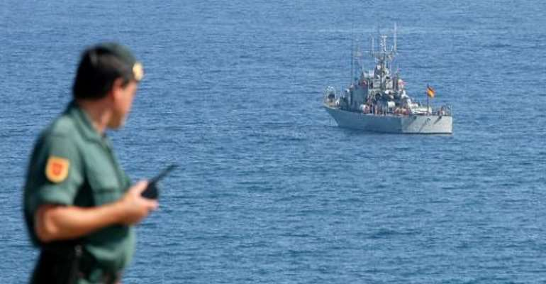 A Spanish Guardia Civil officer watches a Spanish naval frigate by the enclave of Ceuta, October 6, 2005.  By Fidel Raso (AFP/File)
