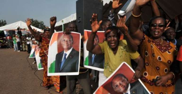 Supporters of Ivorian President Alassane Ouattara hold posters portraying him upon his arrival on April 22, in Guiglo.  By Sia Kambou (AFP/File)