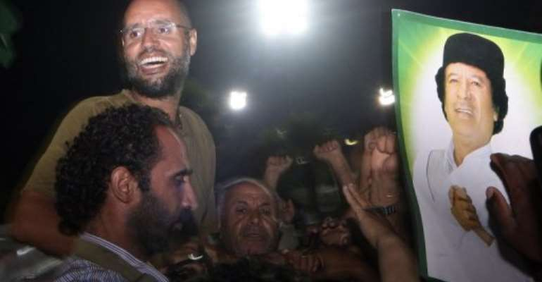 Seif al-Islam Kadhafi, son of Libyan leader Moamer Kadhafi, is surrounded by supporters in Tripoli in 2011.  By Imed Lamloum (AFP/POOL/File)