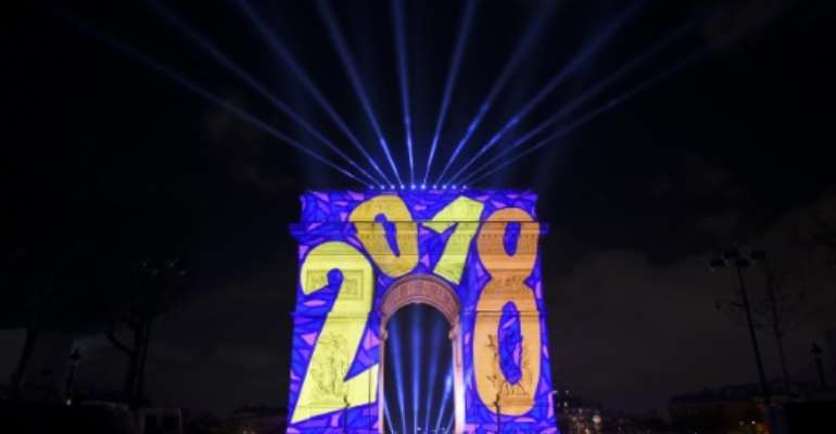 Images are projected on the Arc de Triomphe monument during the New Year celebration in Paris.  By GUILLAUME SOUVANT (AFP)