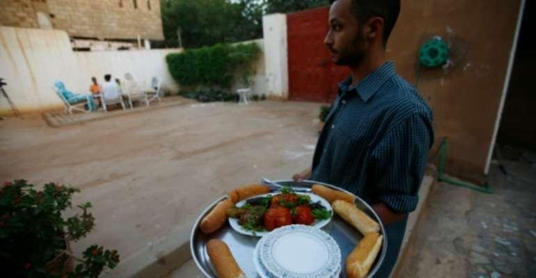 British-Sudanese pharmacist Omer Eltigani serves Sudanese