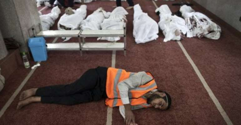 An Egyptian volunteer sleeps on the carpet of a mosque in Cairo where lines of bodies were laid out on August 15, 2013.  By Mahmoud Khaled (AFP)