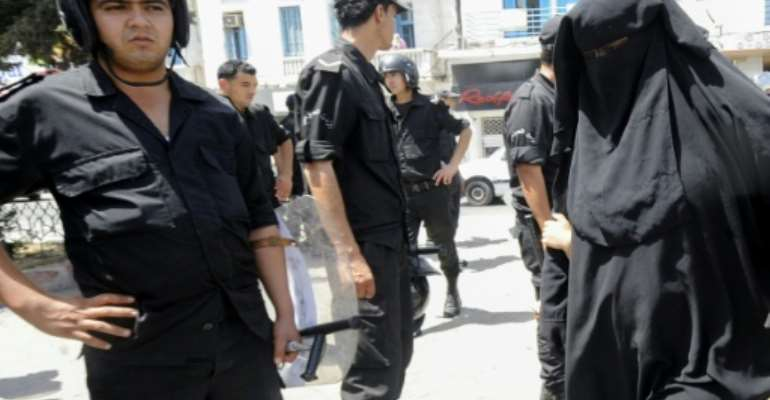 In this file photo from June 2012, a Tunisian woman, wearing a niqab, walks in front of police officers after Friday prayers.  By Fethi Belaid (AFP/File)