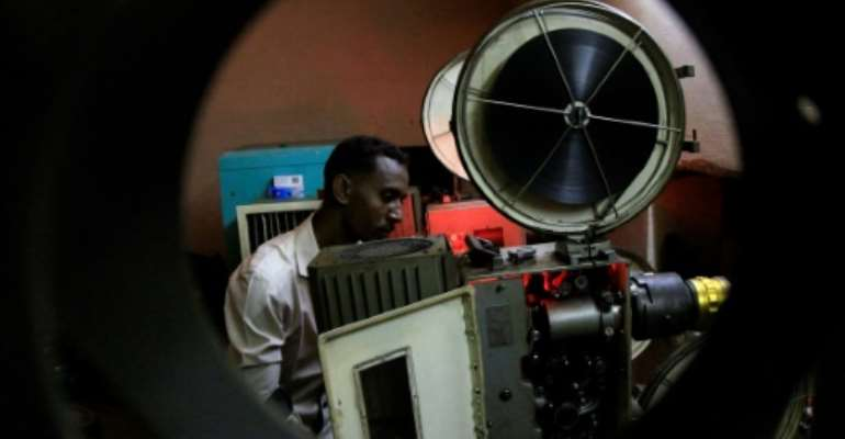 In this picture from 2014, a Sudanese man prepares a film for projection at The Palace of Youth and Children, one of just three functioning cinemas left in the area around the capital Khartoum at the time.  By ASHRAF SHAZLY (AFP/File)