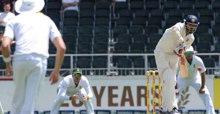 Indian batsman Shikhar Dhawan (right) plays a shot from South African bowler Venon Philander on the first day of their Test match in Johannesburg at Wanderers stadium on December 18, 2013.  By Str (AFP)