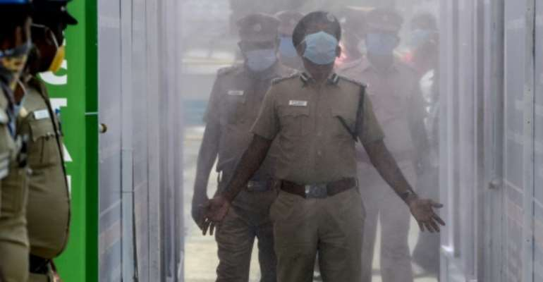Indian police walk through a disinfection tunnel during a government-imposed nationwide lockdown.  By Arun SANKAR (AFP)