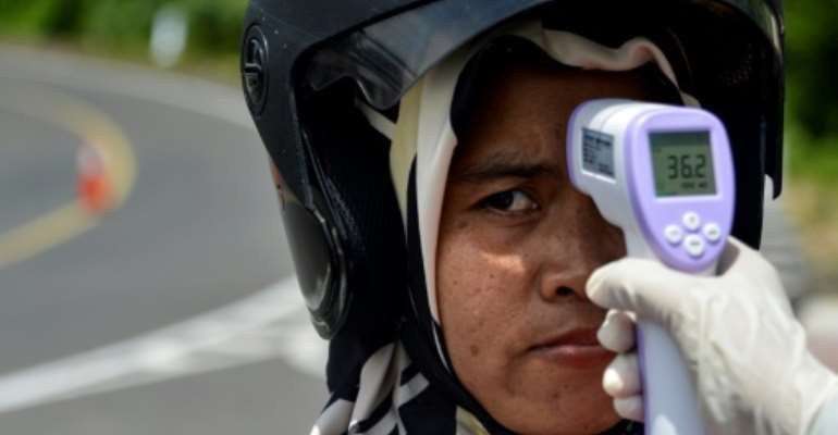 Indonesians in the province of Aceh were having their temperaturs taken.  By CHAIDEER MAHYUDDIN (AFP)