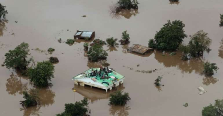 Inland sea: Helicopters are trying to save people stranded on rooftops and in trees.  By Rick Emenaket (Mission Aviation Fellowship/AFP)