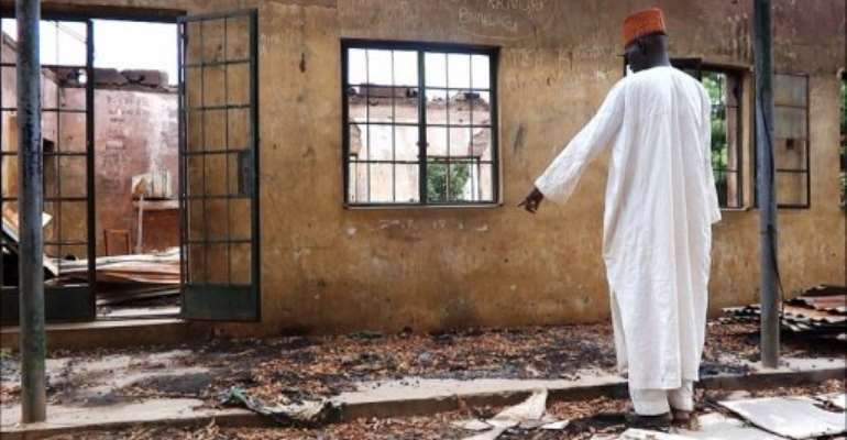 A man inspects a burnt student hostel in the northeast Nigerian Yobe state on August 6, 2013..  By Aminu Abubakar (AFP/File)