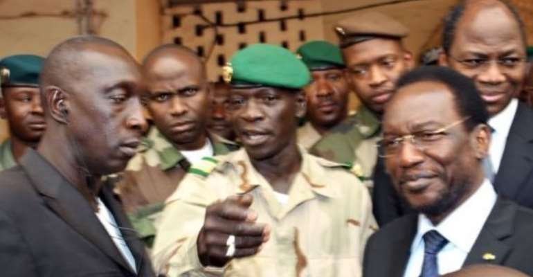 Mali's speaker of parliament Dioncounda Traore (R), with glasses) stands next to Captain Amadou Sanogo (C).  By Habibou Kouyate (AFP)