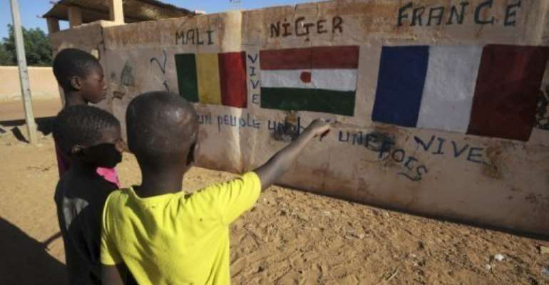 A wall in Gao showing the flags of Mali, Niger and France on February 5, 2013.  By Sia Kambou (AFP/File)