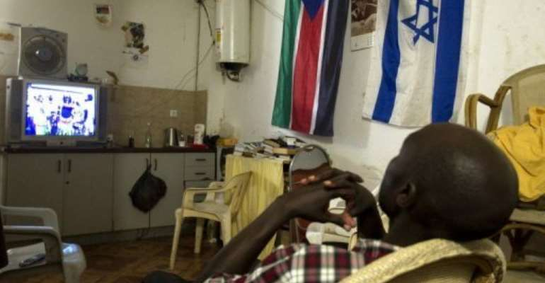 An African migrant from South Sudan watches television in Tel Aviv.  By Jack Guez (AFP/File)