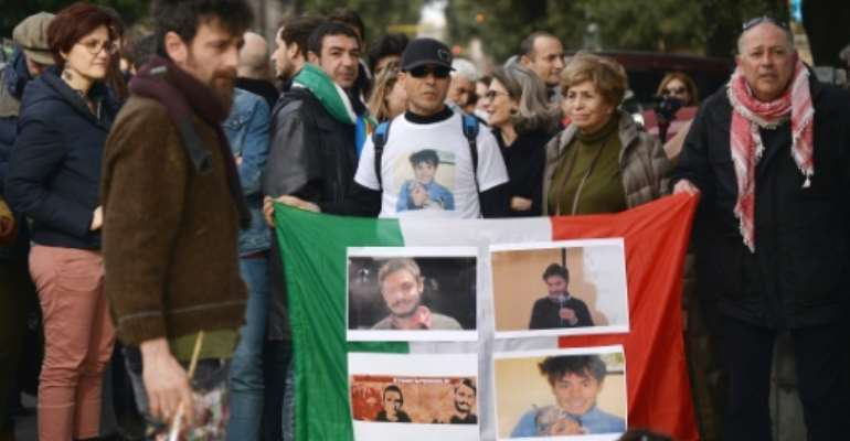 Protesters hold an Italian flag with photos of Giulio Regeni, during a demonstration in front of the Egypt's embassy in Rome, on February 25, 2016.  By Filippo Monteforte (AFP/File)