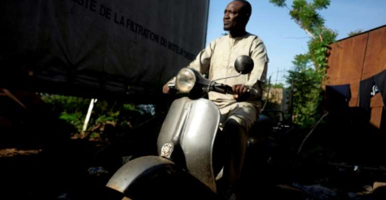 It's love: Seydou Seck and his cherished Vespa.  By MICHELE CATTANI (AFP)