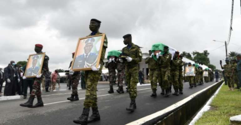Ivory Coast soldiers carry coffins and pictures of their comrades killed in a brazen jihadist attack last month.  By SIA KAMBOU (AFP)