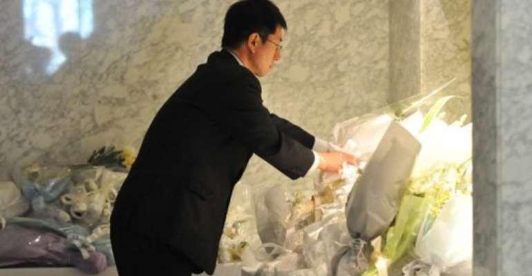 A man offers flowers for Japanese victims of the Algerian hostage crisis in Yokohama, suburban Tokyo on January 24, 2013.  By Kazuhiro Nogi (AFP)