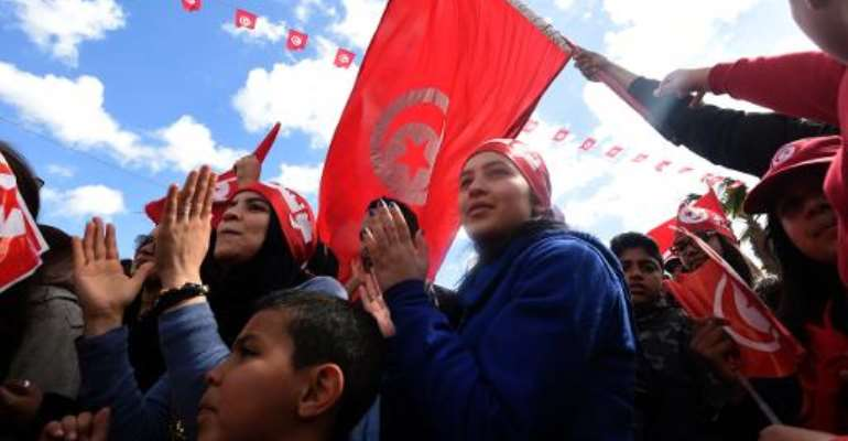Tunisians wave their national flag and chant slogans during a march against extremism outside Tunis' Bardo Museum on March 29, 2015.  By Fethi Belaid (AFP)