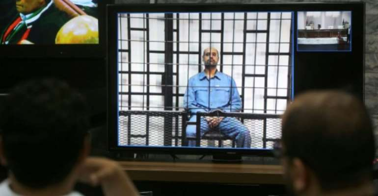 Journalists watch from a press room in Tripoli Seif al-Islam (C), the son of slain Libyan dictator Moamer Kadhafi, answering his judges' questions by video conference from a prison the western Libyan city of Zintan, on May 11, 2014.  By MAHMUD TURKIA (AFP/File)