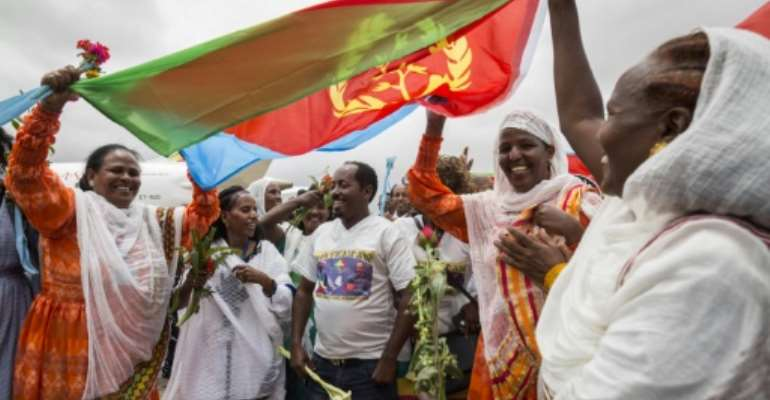 Joy: Eritrean women hold aloft the national flag in July 2018 to welcome passengers arriving from Ethiopia, a key step in the two rivals' path to peace.  By MICHAEL TEWELDE (AFP/File)
