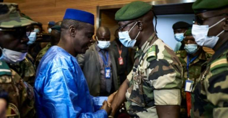 Junta number two Malick Diaw, right, shakes hands with Issa Kaou Djim, a leading figure in the June 5 Movement as talks began.  By MICHELE CATTANI (AFP)