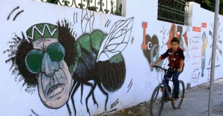 A Libyan boy cycles past graffiti depicting former strongman Moamer Kadhafi painted on a wall in Tripoli,.  By Mahmud Turkia (AFP/File)