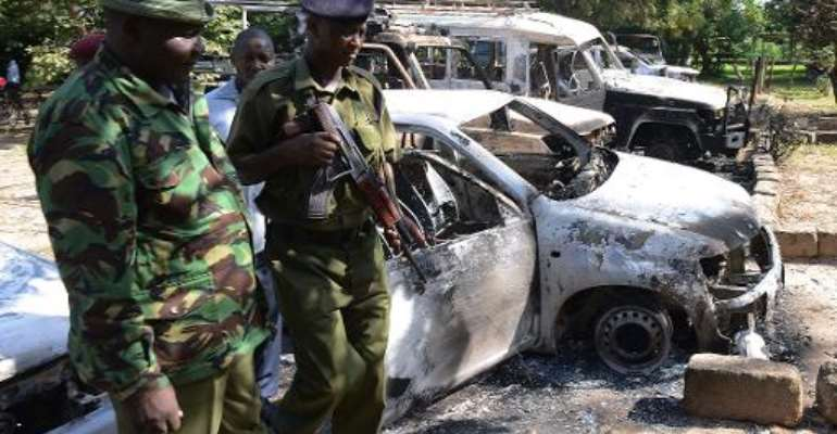 Kenyan police observe the remains of burnt-out cars at a police station in Mpeketoni, in the coastal county of Lamu on June 16, 2014.  By Simon Maina (AFP/File)