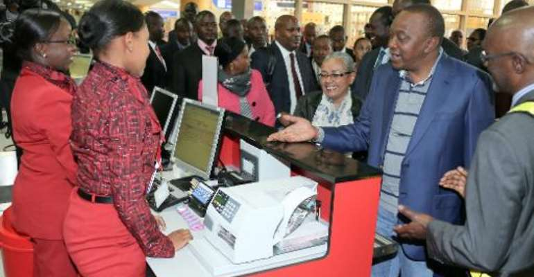 Kenyan President Uhuru Kenyatta (2nd-R) and First Lady Margaret Kenyatta check in alongside other passengers at Nairobi airport as they head to the Hague on October 7, 2014.  By PSCU (PSCU/AFP)