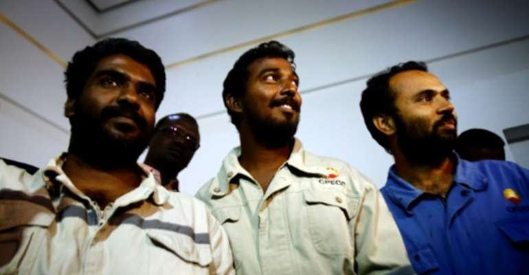 (L to R) Indians Midhun Ganesh and Edward Ambrose and Pakistani Ayaz Hussein Jamali, look on upon their arrival at Khartoum airport on March 30, 2017.  By ASHRAF SHAZLY (AFP)