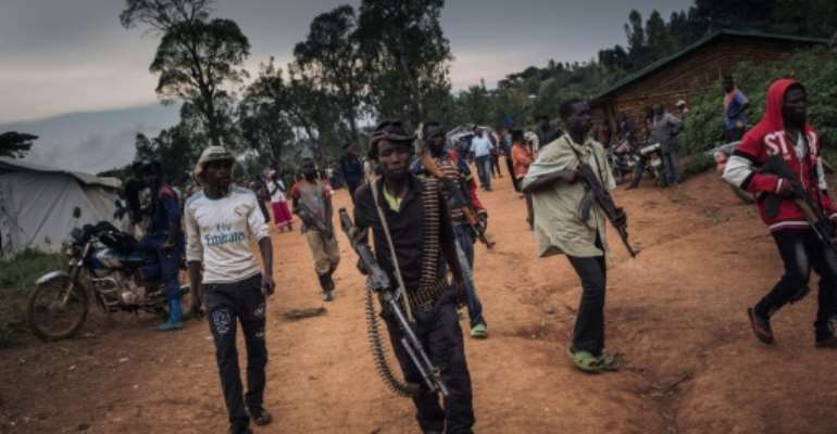Lendu militiamen at a meeting with former warlords in the village of Wadda.  By ALEXIS HUGUET (AFP)
