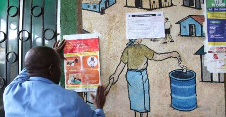 A nurse places an information sign about Ebola on a wall of a public health centre in Monrovia, July 31, 2014.  By  (AFP/File)