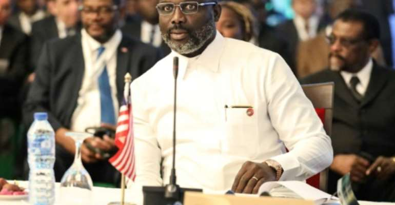 Liberian President George Weah is under growing pressure from the opposition over his handling of the country's economic crisis.  By Kola SULAIMON (AFP)