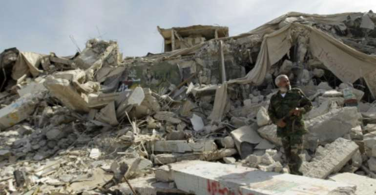 A Libyan fighter walks amidst rubble.  By Joseph Eid (AFP/File)